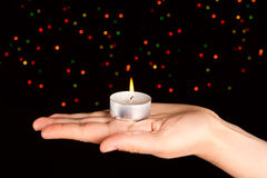 Candle with many-colored sparkles on hand. Stock Images
