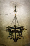 8 candle medieval chandelier hanged by chains over a pulley stock image