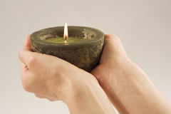 Candle in my Hands. Two hands holding a large candle Royalty Free Stock Images