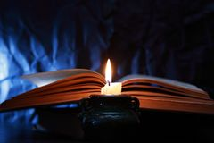 Candle Near Book. Still life with lighting candle near old book on dark blue background stock photos