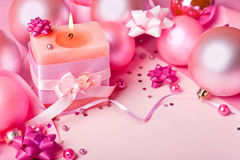 Candle and New Year's spheres in pink tones Royalty Free Stock Photo