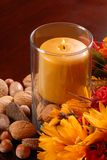 Candle with nuts and flowers Stock Photo