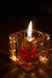 Candle o burning na obscuridade no suporte de vidro no fundo preto, fotos de stock