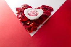 Candle o coração no coração do fundo branco vermelho do canto das pétalas cor-de-rosa Fotografia de Stock Royalty Free