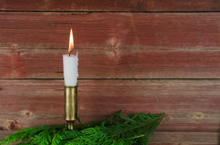 Candle at old barn wall and green decoration Stock Image