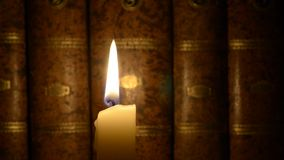 Candle and old books stock video