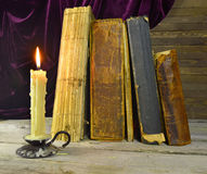 Candle and old books. Still life with old books and single burning candle on the table Royalty Free Stock Photos