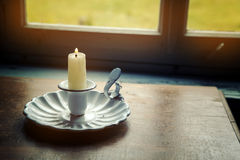 Candle and old candle holder by the window. Closeup of candle and old candle holder by the window Stock Photography
