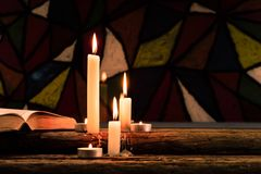 Candle on a old oak wooden table.  Beautiful Stained-glass windows background.Religion concept. Stock Photography