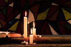 Candle on a old oak wooden table.  Beautiful Stained-glass windows background.Religion concept. Stock Photo