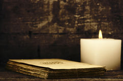Candle and old papers. Closeup of a burning candle and a pile of old papers Royalty Free Stock Photography
