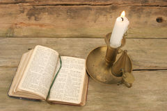 Candle and old prayer book. Old prayer book and candle on background of rustic wood Stock Photos
