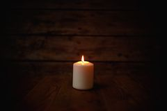 Candle on old wooden background.  Stock Image