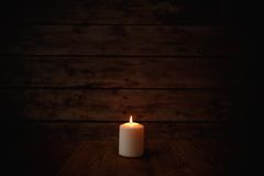 Candle on old wooden background.  Royalty Free Stock Image