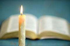 Candle with Open Bible in Background Royalty Free Stock Photos