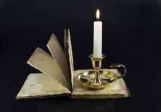 Candle with open book. Burning candle with the open book in the darkness Royalty Free Stock Photos