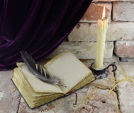 Candle with open book. Burning candle with open book and quill in gothic castle background Royalty Free Stock Photo