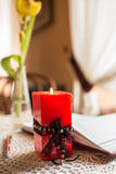 Candle, open book, pen. Red candle burns on a background of an open book with a red pen royalty free stock images