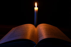Candle and opened book Stock Photos