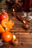 Candle, orange fruit, apple, cinnamon sticks near mulled wine on wooden background. Christmas decoration. New year. Stock Photo
