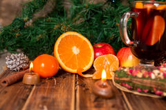 Candle, orange fruit, apple, cinnamon sticks near mulled wine on wooden background. Christmas decoration. New year. Royalty Free Stock Photos