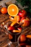 Candle, orange fruit, apple near mulled wine on wooden background. Christmas decoration. New year. Royalty Free Stock Image