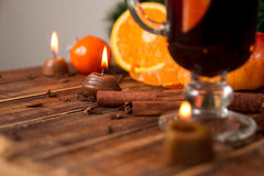 Candle, orange fruit, cinnamon sticks near mulled wine on wooden background. Christmas decoration. New year. Copy space. Stock Image