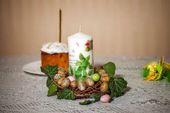 Candle and by the painted eggs on background easter cake Royalty Free Stock Image
