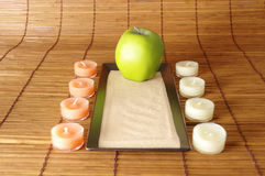 Candle path. A candle path is leading up to a green apple Stock Image