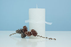 Candle and pine cones. White glittered candle with ribbon around it against a blue and white background with a stick and pine cones Stock Images