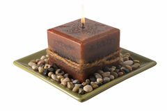 Candle on plate with stones - lit Royalty Free Stock Image