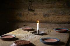 Candle  and plates on the table Stock Photos