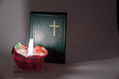 Candle and prayer book. In dark room Stock Photos