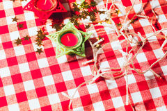Candle on red checkered tablecloths and garland Stock Photos