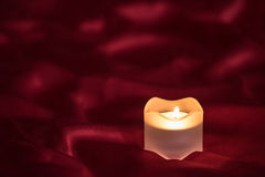 Candle on the red cloth Stock Photography