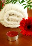 Candle, red gerber and white towel Stock Photos