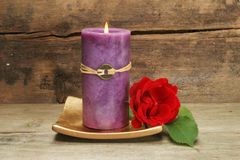 Candle and red rose. Purple Feng Shui candle and red rose Royalty Free Stock Image