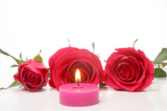 Candle and red roses. Burning candle and three red roses Royalty Free Stock Photography