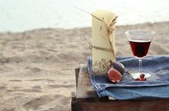 Candle and red wine on the beach Stock Image
