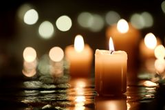 Candle with reflection. Burning candle with reflection against candlelight background Stock Image