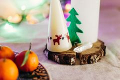 Candle with reindeers and christmas tree on rustic christmas tab Stock Image