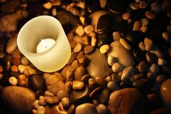 Candle and Rocks Stock Images