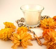 Candle and Rosary. A white candle and rosary with orange flowers Royalty Free Stock Images