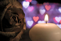Candle with rose flower on bokeh hearts background. Vintage style. Stock Images