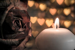 Candle with rose flower macro on bokeh hearts background. Vintage style. Royalty Free Stock Photography