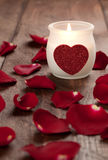 Candle and rose petals. A candle with heart and rose petals Royalty Free Stock Photography