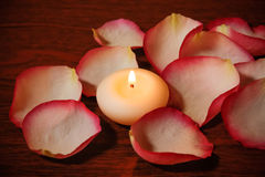 Candle and rose petals. Selective focus on candle. Candle and rose petals on wooden table. Selective focus on candle Royalty Free Stock Photos