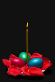 Candle, rose petals and three Easter eggs on a plate, isolated Royalty Free Stock Image