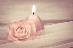 Candle and rose. Pink burning candle and rose over white fabric background Stock Image