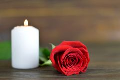 Candle and rose on wooden background. Candle and red rose on wooden background Royalty Free Stock Photography